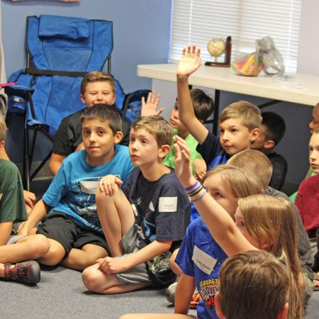 Kids Sitting on floor raising hands at church group